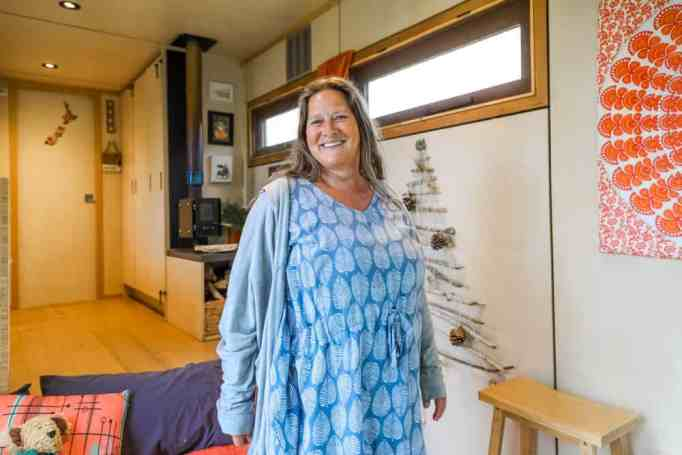 A woman standing inside her off-grid tiny house truck