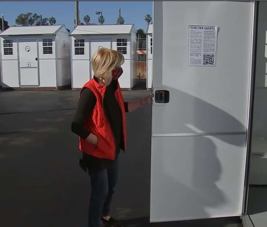Woman inspecting one of the tiny homes