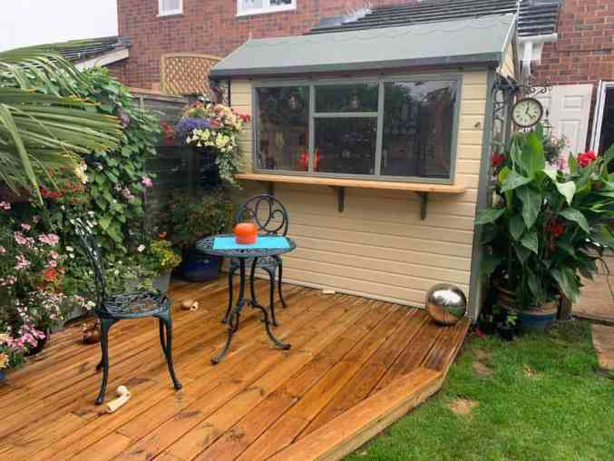 Modern backyards: A shed with wooden outdoor flooring.