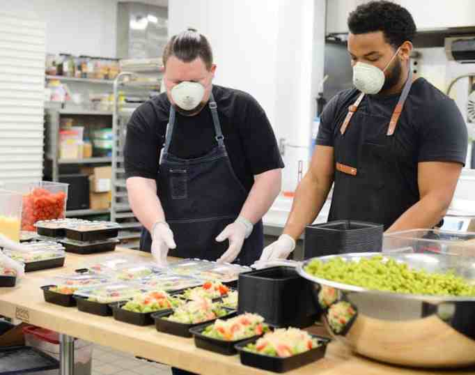 Two masked men preparing food in a kitchen