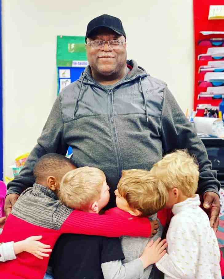 Raymond Brown being hugged by four little boys