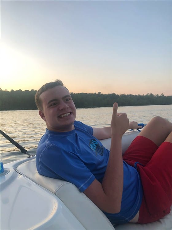 Ryan Lowry on a boat doing the thumbs-up gesture