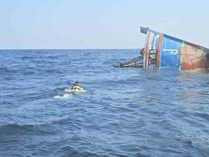 A Navy sailor swimming toward a sunken ship
