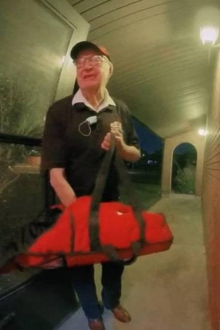 An elderly man delivering pizza