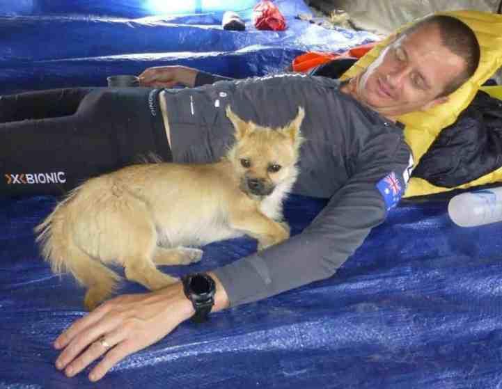 Dion Leonard and Gobi snuggling on a sleeping pad