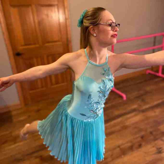 The hopeful Sports Illustrated model Mikayla Holmgren wearing a blue dress doing a ballerina pose