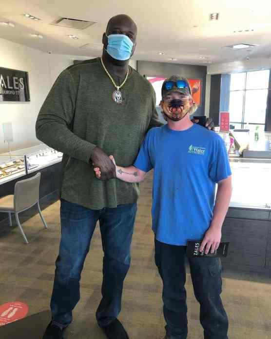 Shaquille O'Neal posing for a photo beside a man inside a Zales store