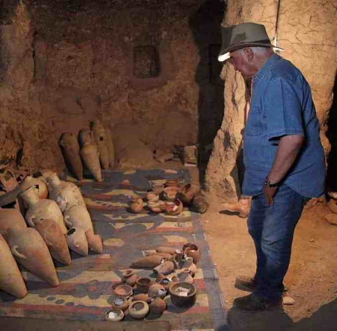 Dr. Zahi Hawass looking at ancient pottery unearthed from the lost golden city in Egypt
