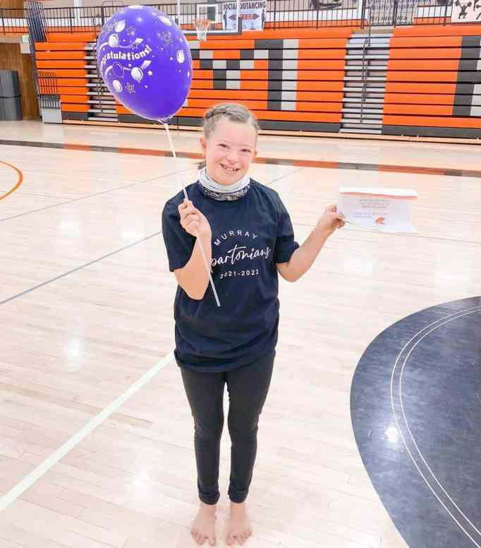 Bree Cox holding a balloon on her right hand and a certificate on the other