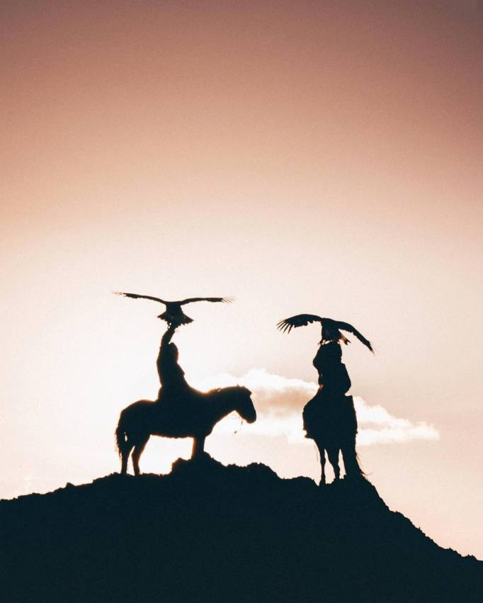 A silhouette of two eagle hunters and their eagles