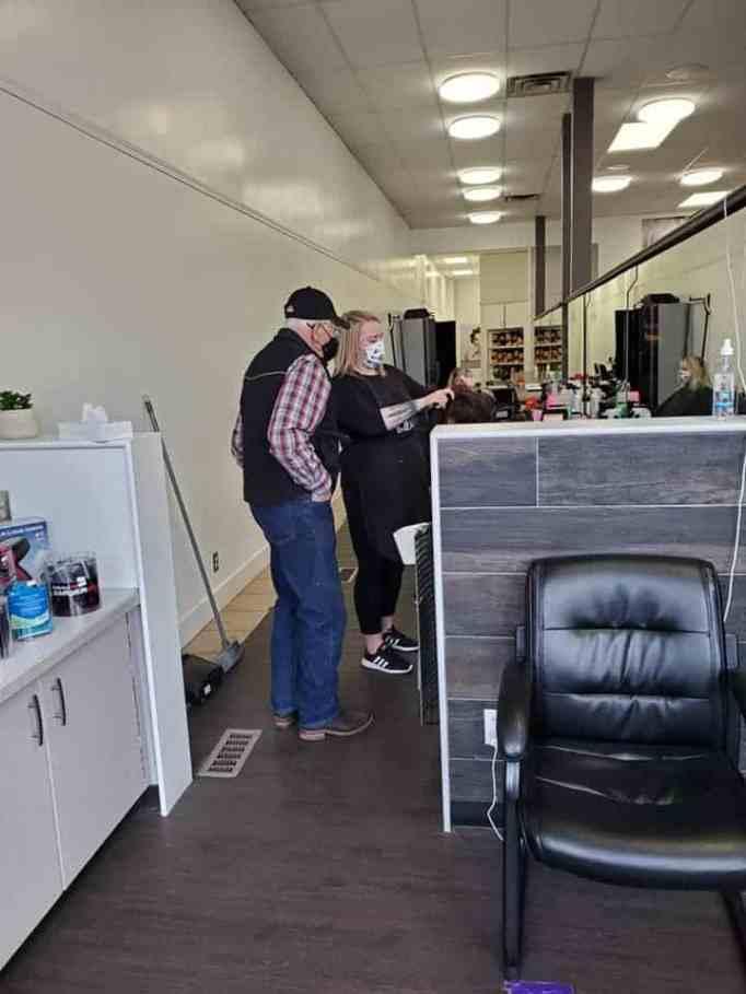 An elderly man watching a woman curl a mannequin's hair