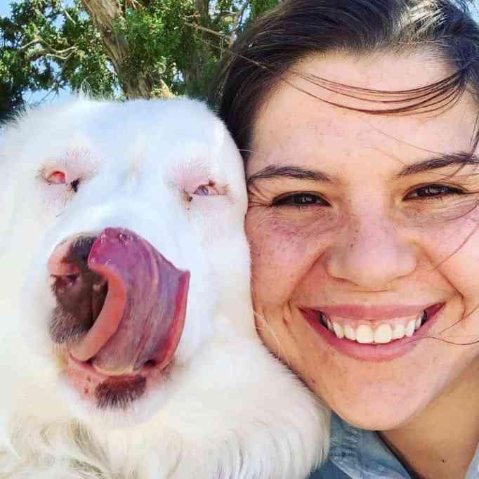 Hayden Kristal smiling and her dog Bitsy licking her nose
