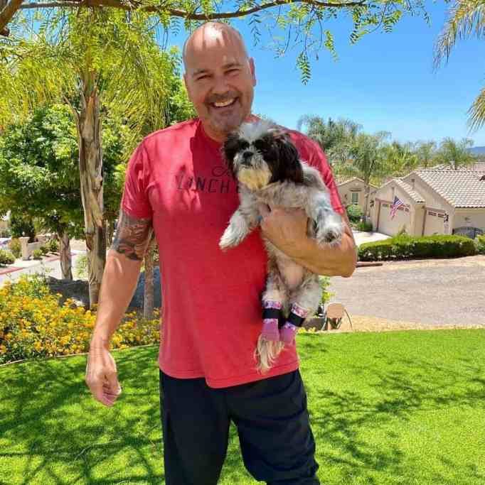 Detective James Hunter holding a double amputee shih tzu that he recently adopted