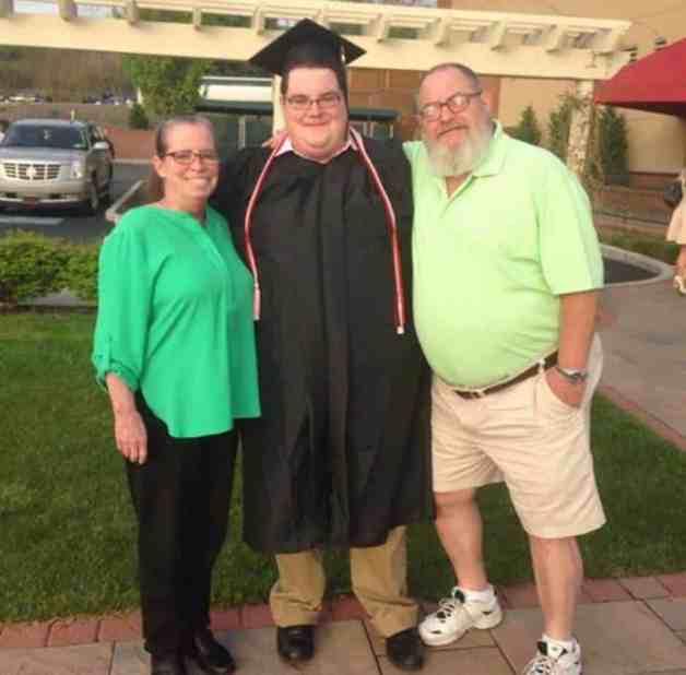 Luke graduation photo with parents