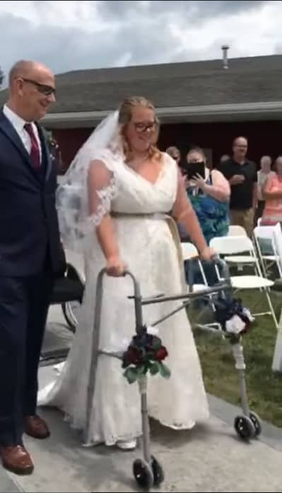 Brittney Bedwell walking down the aisle with the help of her father and a walker