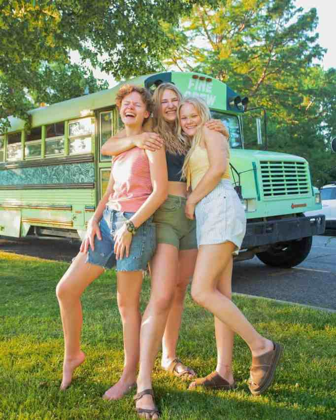 Bekah King, Abi Roberts, and Morgan Tabor posing in front of their BAM bus