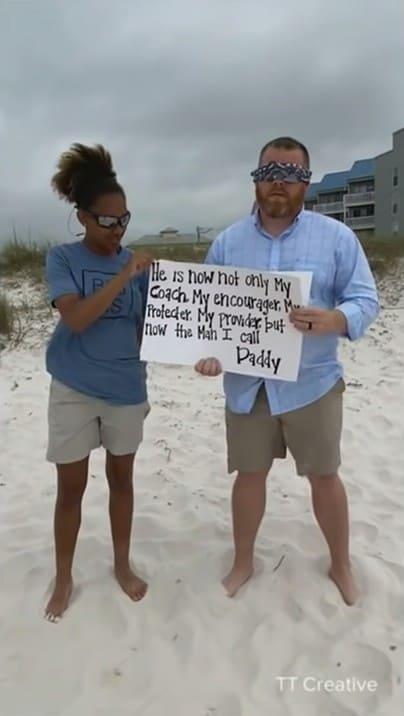 Daniel Donaldon holding up a sign with Alecia guiding him