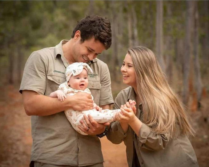 Chandler Powell holding Grace Warrior while Bindi Irwin holds the baby's feet