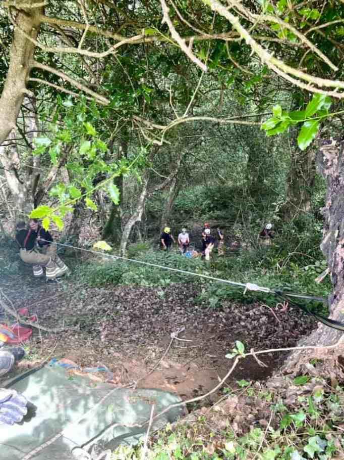 Rescuers retrieving elderly woman who fell down into a deep ravine