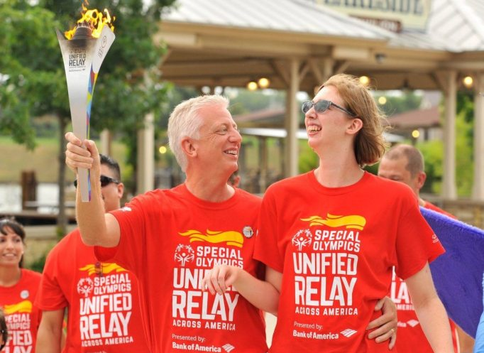 Gordon and Morgan carry a torch at a Special Olympics event