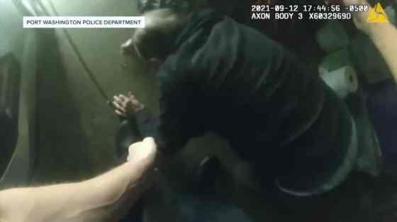 An elderly man crawling on a garage floor
