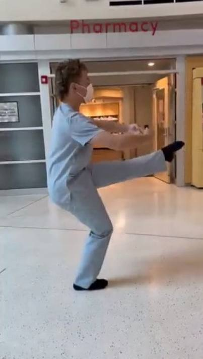 A hospital employee performing ballet in the lobby