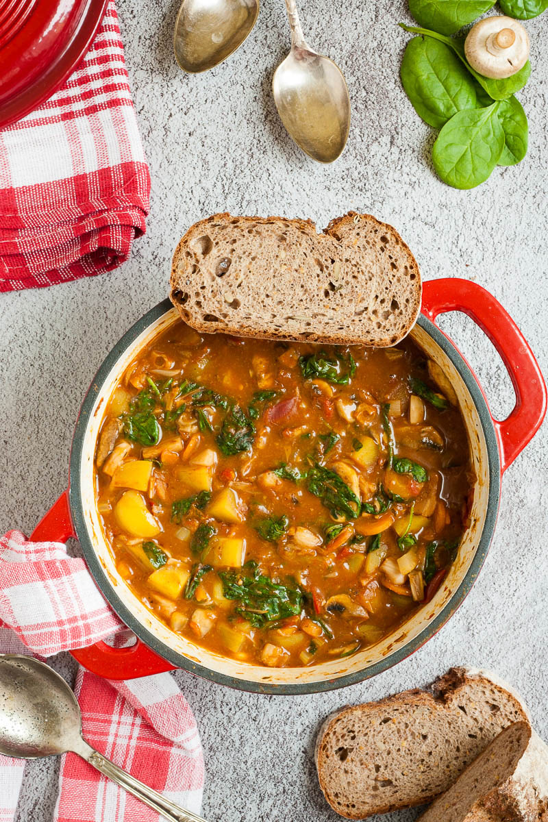 Red Dutch oven from above with a stew where you can see chopped potatoes, spinach leaves, carrot slices, tomatoes, and mushroom slices. A slice of bread is place on the rim. Red white table clothes are around with slices of bread, spinach leaves and spoons
