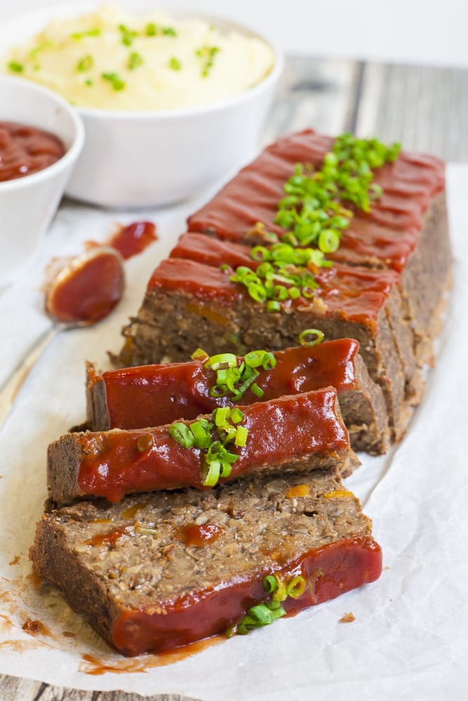 Vegan lentil loaf on parchment paper from above with maple tomato glaze and chopped spring onion.