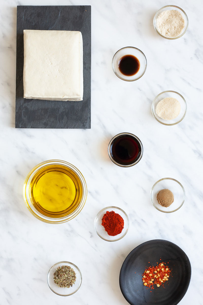 All ingredients for a tofu steak are separated into lots of glass bowls: 2 bowls with dark black sauce, one with oil, 4 with light yellow-white powder and one with a red chili flakes. And there is a block of firm tofu on a black plate