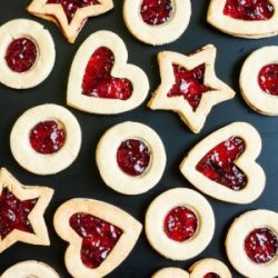 Light brown cookies in shapes of heart, star and circle filled with red jam is scattered around on a black surface.