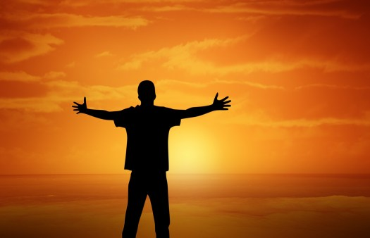 Man standing in front of dawn sun with arms stretched as if to embrace life!