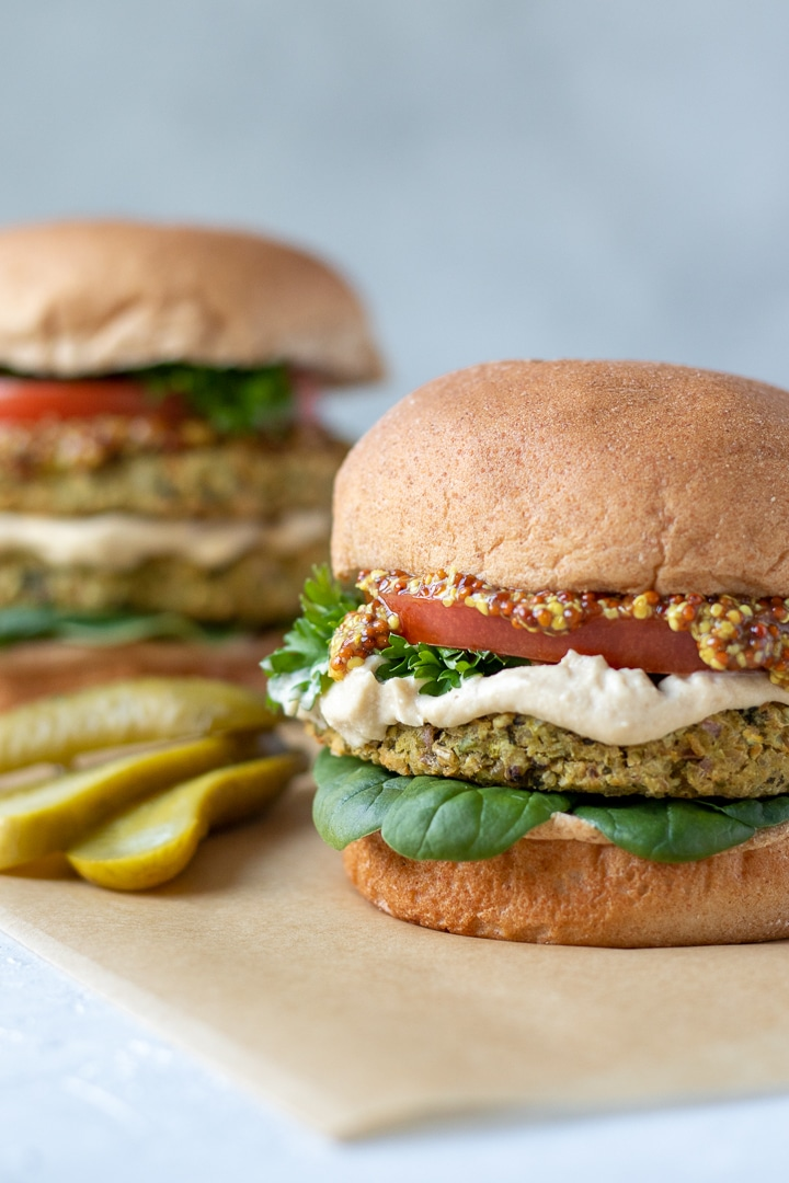 Tabbouleh-Inspired Bean Burgers on buns with spinach, tomato, hummus and a pickle