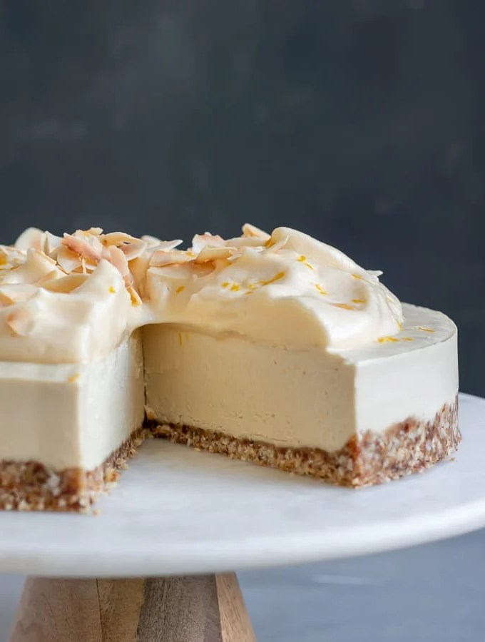 Meyer Lemon Vegan Cheesecake on marble and wood cake stand
