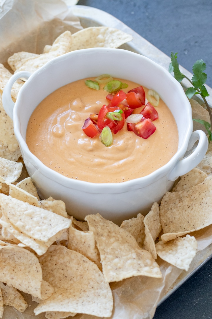 Easy Vegan Queso in a white bowl topped with tomato and green onion