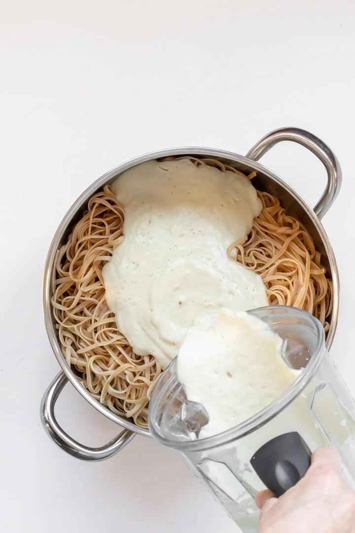 pouring alfredo sauce onto pasta noodles