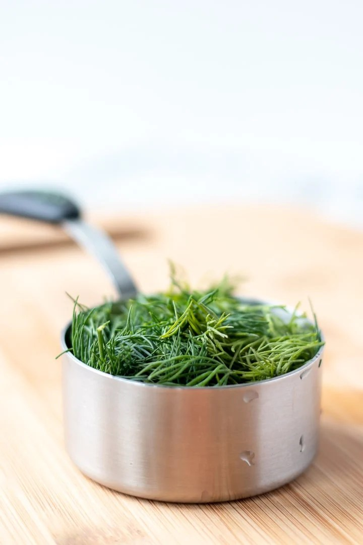 Half cup measuring cup filled with dill