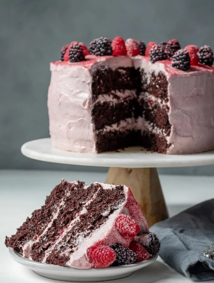 Vegan Chocolate Layer Cake on a cake stand and a slice on a plate