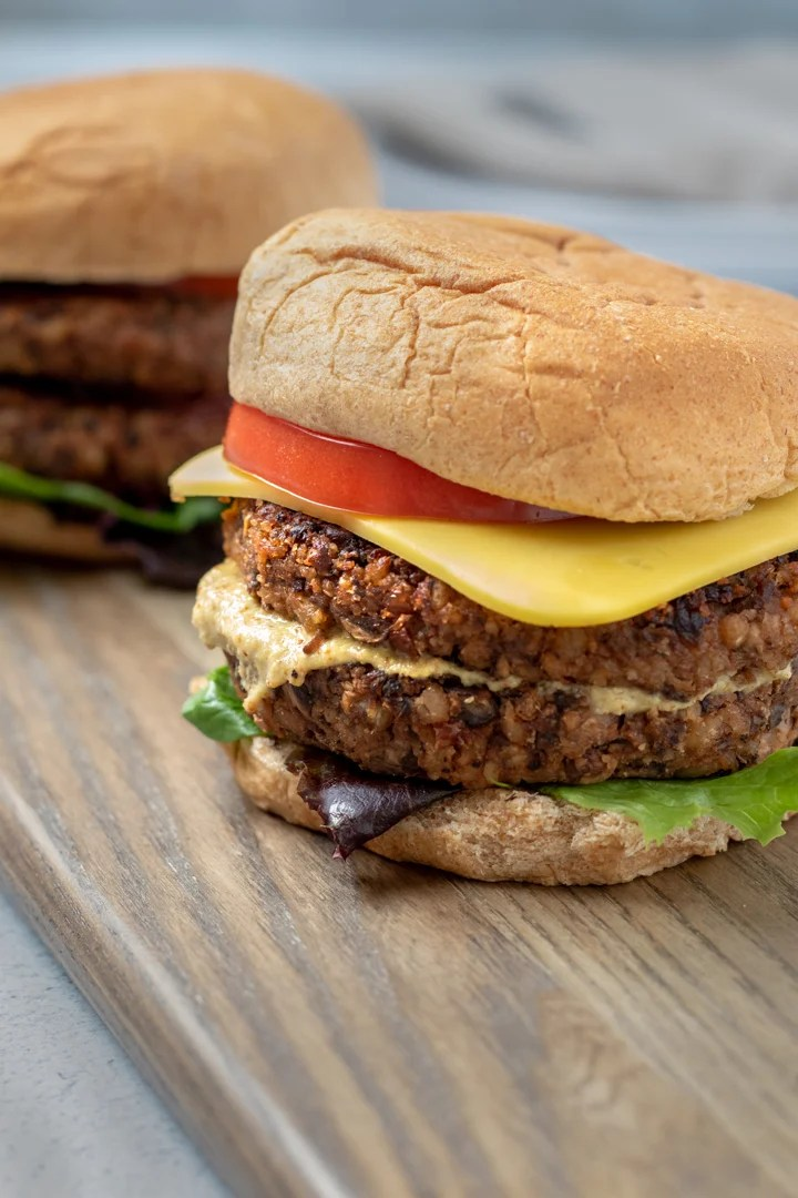 burgers on a bun with tomato, vegan cheese, lettuce and mustard
