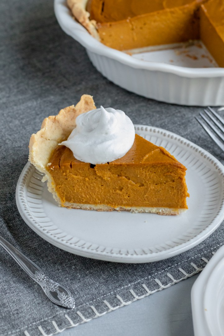 deep dish vegan pumpkin pie topped with So Delicious coconut whipped topping