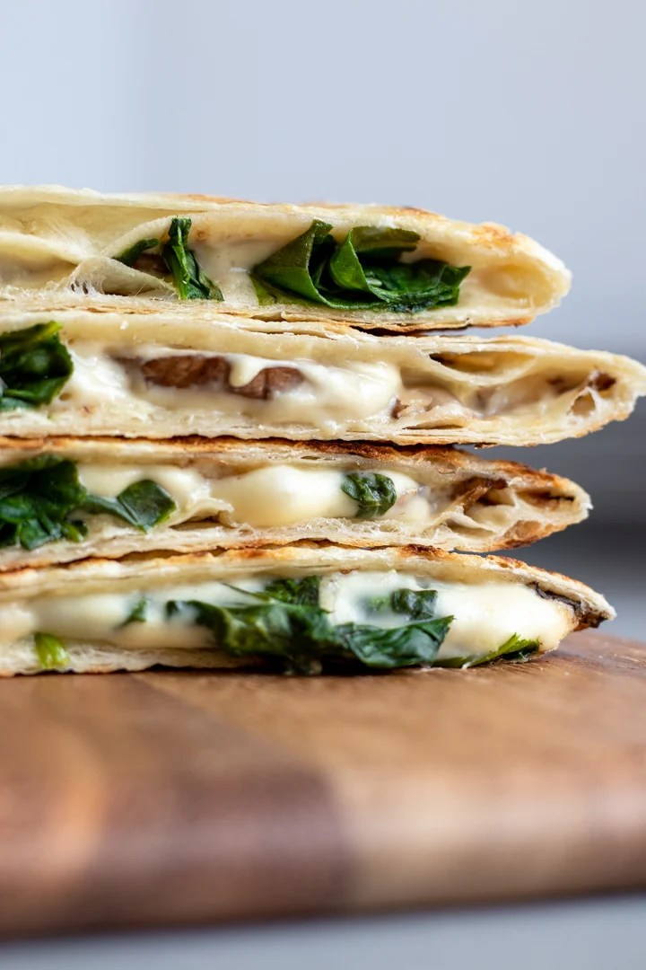 a stack of vegan quesadillas filled with homemade cheese, spinach and mushrooms