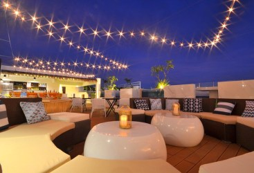 Ferra Hotel Boracay rooftop restaurant, with soft seating and glossy white tables, light by fairy lights