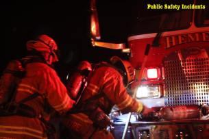 Firefighters check their gear before beginning to battle the blaze. Robert Carter photo