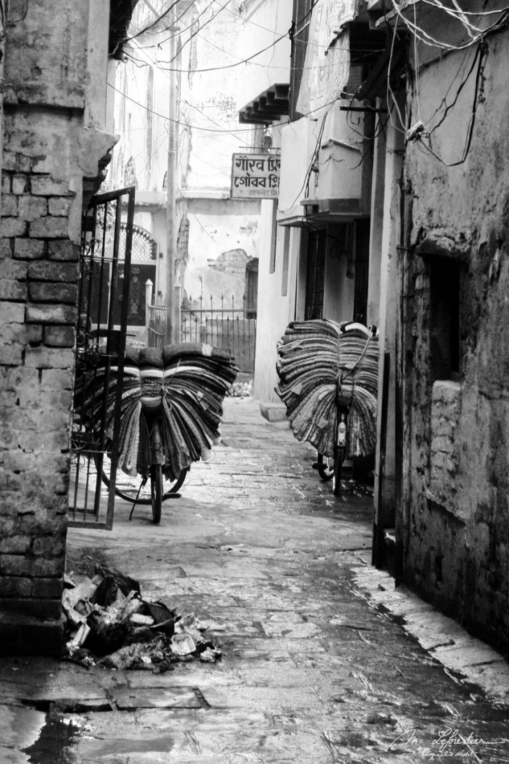 silk on bikes in Varanasi India black and white