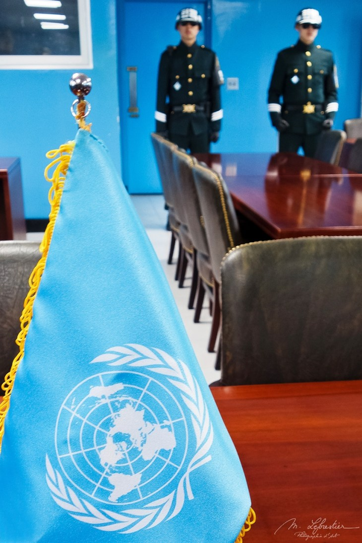 UN flag on the negotiation table in the JSA with North Korean soldiers in the background