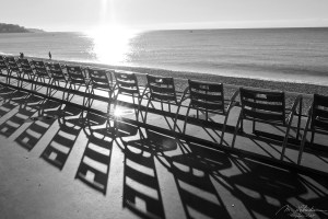 Chairs and their reflections on the Promenade des Anglais in Nice France