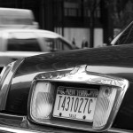 close up of a tag in new york city with a taxi in the back NYC USA black and white