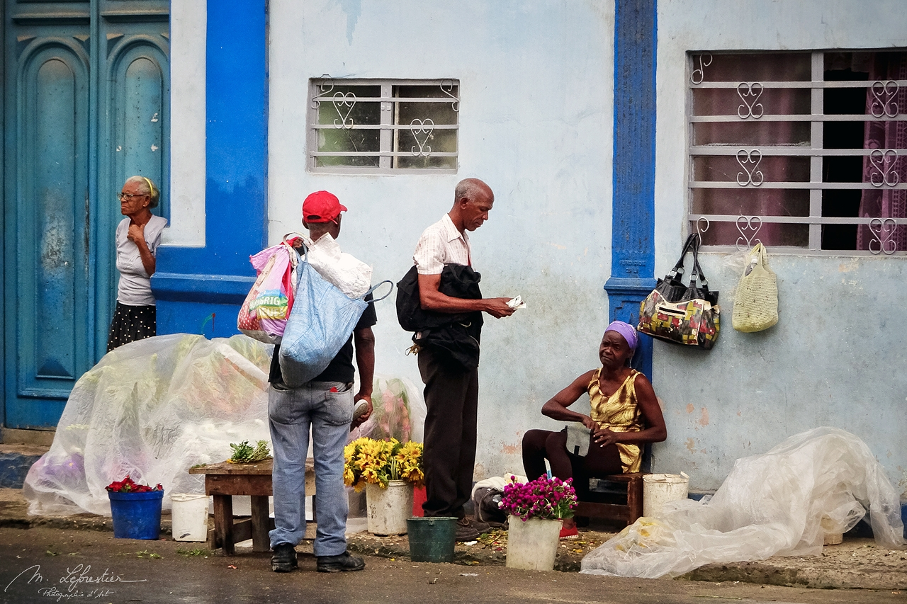 a man is buying flowers from a woman in a street of la Havana Cuba