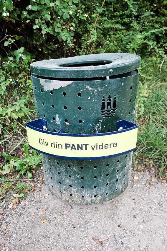 a green bin by grass in Copenhagen Denmark Giv din PANT videre