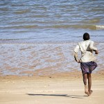 man on the beach running freely towards the sea in Beira Mozambique