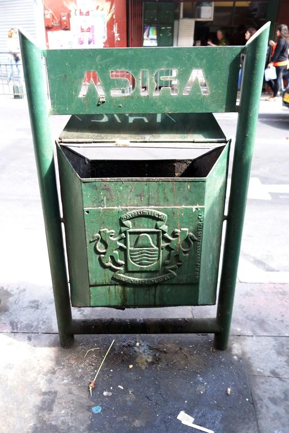 a green litter bin in a street in Arica Peru